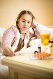 在床上和看thermom的小病的女孩画象  免版税库存照片