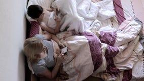 在床上在毯子下和使用智能手机的母亲和儿子,搜寻互联网,写消息和使用 股票录像