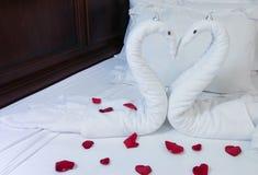 在床上塑造的两只毛巾天鹅 免版税库存照片