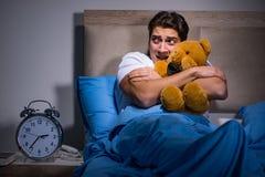 在床上惊吓的年轻人 免版税图库摄影