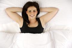 在床上放置的妇女放松了注视着照相机微笑 免版税库存照片
