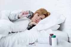 在床上检查温度的病的妇女与温度计狂热微弱的痛苦冷的冬天流感病毒 免版税库存图片