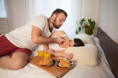 在床上用早餐一对已婚夫妇早晨在卧室 免版税库存照片
