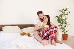 在床上用早餐一对已婚夫妇早晨在卧室 免版税库存图片
