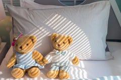 在床上的一个棕色夫妇玩具熊倾斜的白色枕头 库存照片