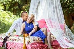 在床上的一对夫妇在草甸 免版税库存照片