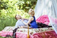 在床上的一对夫妇在草甸 免版税图库摄影