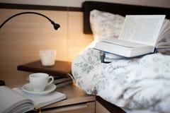 在床上的一本开放书 书和咖啡杯在nightstand 免版税库存照片