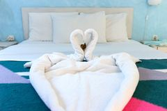 在床上的两只毛巾天鹅在旅馆客房 免版税库存图片