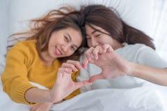 在床上的亚洲女同性恋的LGBT夫妇位置和做心脏递形状wi 免版税库存照片