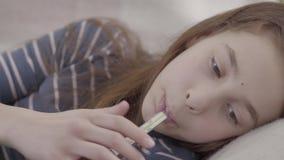 在床上的十几岁的女孩画象采取在她的嘴的一个温度计并且测量温度 r 股票视频