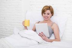 在床上的可爱的妇女使用数字式片剂垫读书早晨网上新闻在食用的互联网咖啡 免版税库存图片