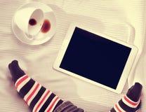 在床上的咖啡和片剂计算机 免版税图库摄影