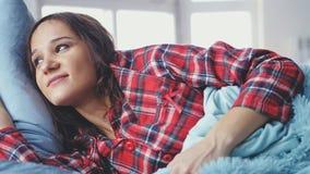 在床上的困少妇叫醒神色在窗口和微笑 免版税库存照片