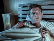 在床上的失眠的年轻人注重了并且惊吓了遭受的恶梦和恐怖坏梦想劫掠的鸭绒垫子害怕的和parano 库存照片