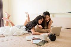 在床上的女同性恋的夫妇计划假期旅行 免版税库存照片