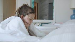 在床上的女孩在一部毯子和观看的动画片下在平板电脑 股票录像