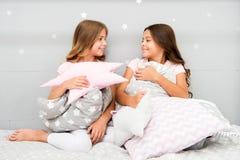 在床上的女孩孩子与逗人喜爱的枕头 睡衣派对概念 乐趣女孩有希望 诚实少女的秘密和 库存照片