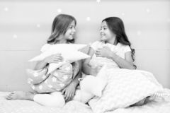 在床上的女孩孩子与逗人喜爱的枕头 睡衣派对概念 乐趣女孩有希望 诚实少女的秘密和 图库摄影
