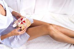 在床上的女孩拿着一件礼物 免版税库存照片