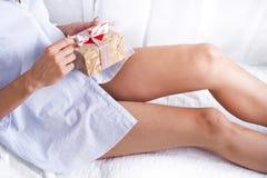 在床上的女孩拿着一件礼物 库存照片