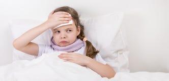 在床上的女孩有头疼,在右边那里是题字的一个地方 免版税库存照片