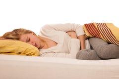 在床上的妇女握腹部由于在stomac的痛苦 图库摄影
