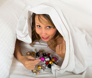 在床上的妇女秘密地吃糖果 库存照片