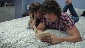 在床上的妇女笑的一会儿人看书 股票视频