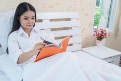 在床上的妇女,当读书时 图库摄影