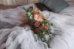 在床上的婚礼花束 库存图片