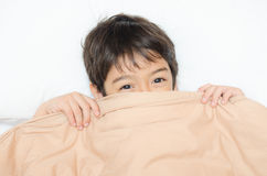 在床上的小男孩位置与一揽子盖子半面孔 库存照片