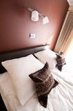在床上的布朗枕头与墙壁照明设备 免版税库存照片