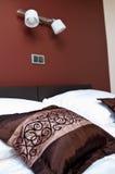在床上的布朗枕头与墙壁照明设备 免版税库存图片
