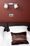 在床上的布朗枕头与墙壁照明设备 图库摄影