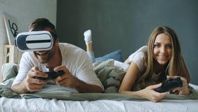 在床上的年轻夫妇打与控制器和VR耳机的电子游戏 免版税图库摄影