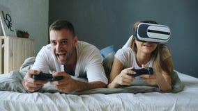 在床上的年轻夫妇打与控制器和VR耳机的电子游戏 库存图片