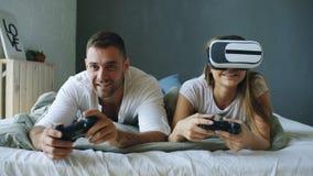 在床上的年轻夫妇打与控制器和VR耳机的电子游戏 免版税库存照片