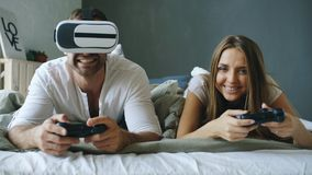 在床上的年轻夫妇打与控制器和VR耳机的电子游戏 免版税库存图片