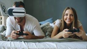 在床上的年轻夫妇打与控制器和VR耳机的电子游戏 库存照片