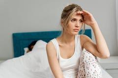 在床上的年轻夫妇;问题在卧室 免版税库存照片