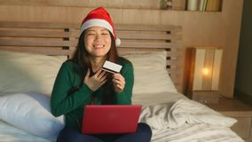 在床上的年轻愉快的美丽的亚裔美国人女孩在圣诞老人使用信用卡的圣诞节网络购物的帽子和手提电脑 免版税库存图片