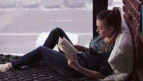 在床上的年轻沉思妇女阅读书由窗口俯视的城市街道 股票录像
