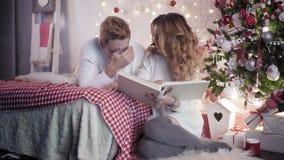 在床上的年轻美丽的看的象册在圣诞树附近 股票视频