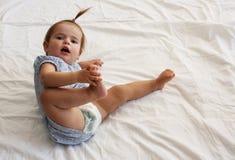 在床上的微笑的女婴 免版税库存照片