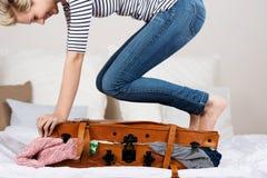 在床上的快乐的妇女包装手提箱 免版税库存照片
