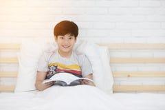在床上的愉快的亚洲男孩读书故事书 库存照片