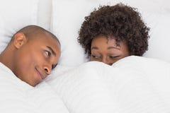 在床上的愉快的夫妇在鸭绒垫子下 库存图片