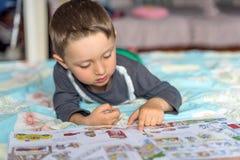 在床上的愉快的欧洲男孩读书故事书与太阳光在早晨 免版税库存图片