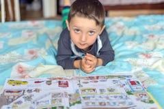 在床上的愉快的欧洲男孩读书故事书与太阳光在早晨 免版税库存照片